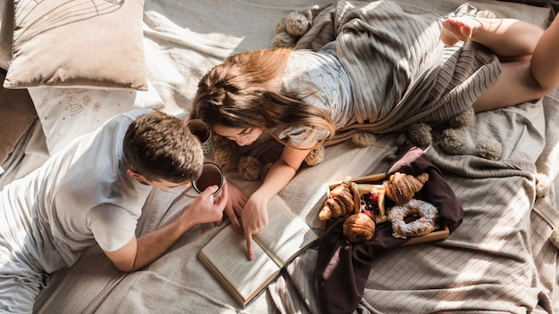 An elevated view of couple lying on bed reading book Free Photo