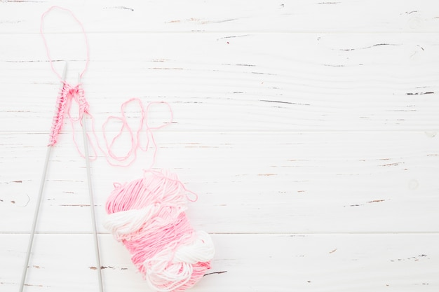 Elevated view of crochet with pink yarn on wooden backdrop Free Photo