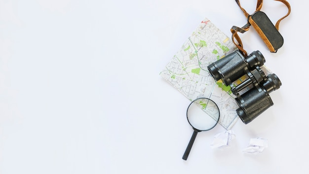Elevated view of crumpled tissue paper; map; binoculars and magnifying glass on white backdrop Free Photo