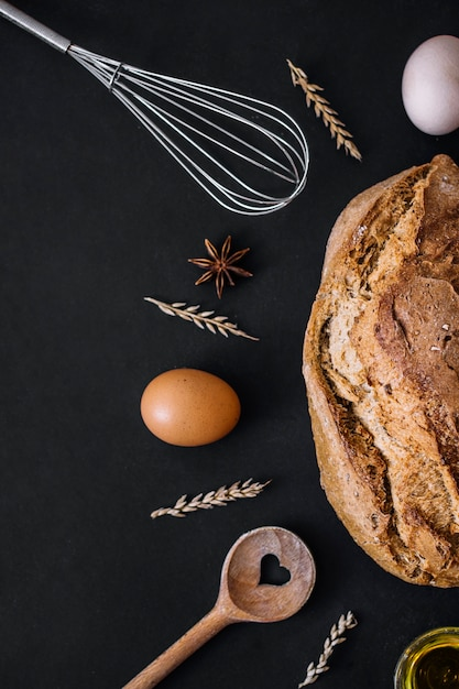 Elevated view of delicious bread with baking ingredients and utensils on black backdrop Free Photo