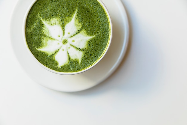 An elevated view of delicious matcha latte flower art cup on saucer over white background Free Photo