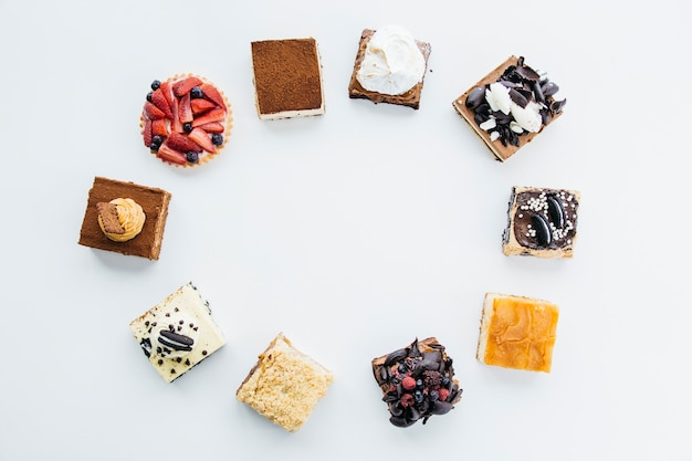 Elevated view of delicious pastries forming frame on white background Free Photo