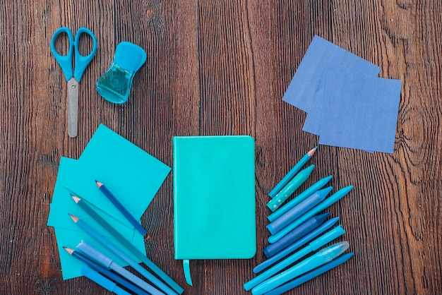 Elevated view of diary; drawing colors; scissor and colorful papers on textured wooden surface Free Photo