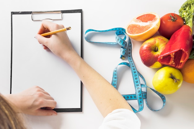 Elevated view of a dietician's hand writing on clipboard with pencil Free Photo