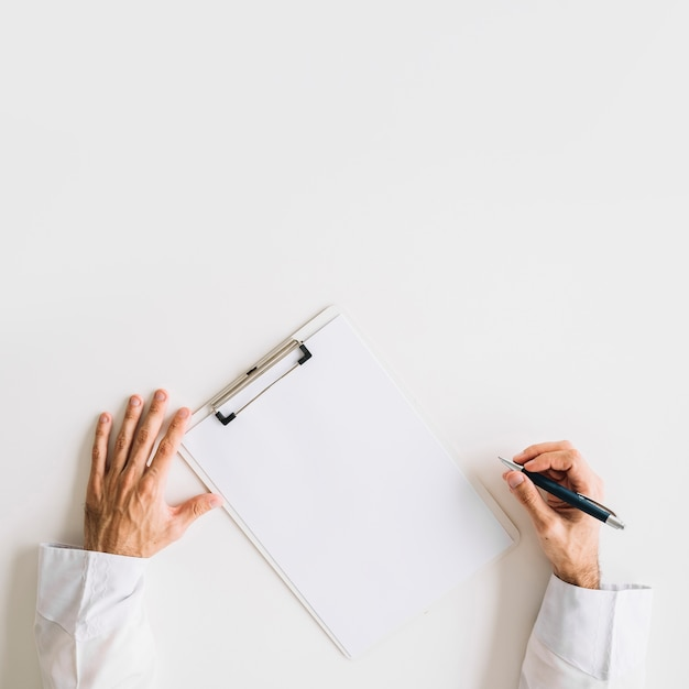 Elevated view of doctor's hand with blank white paper Free Photo