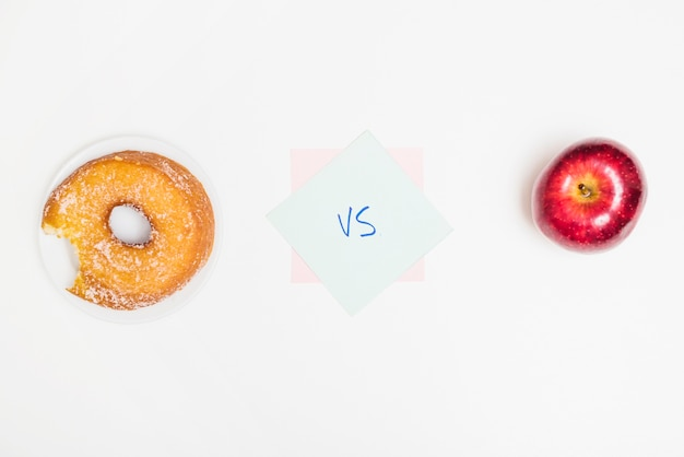 Elevated view of donut versus apple on white surface Free Photo