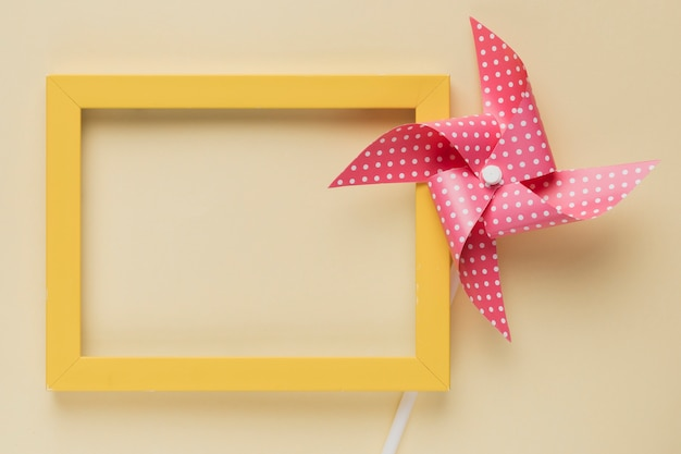 Elevated view of dotted pinwheel and yellow frame on beige background Free Photo