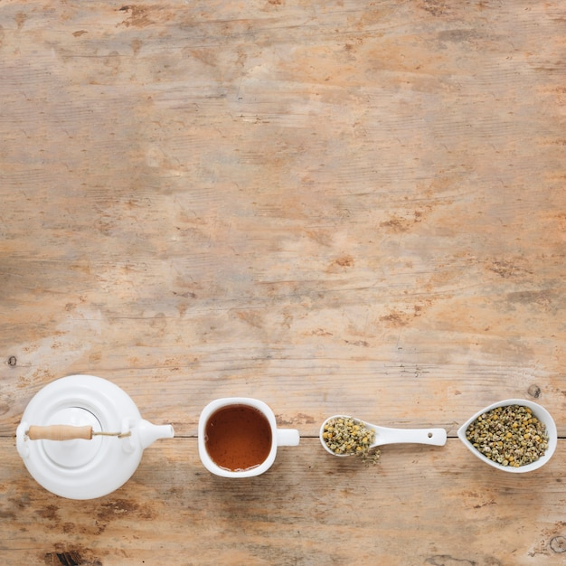 Elevated view of dried chinese chrysanthemum flowers; teapot and lemon tea arranged in a row on table Free Photo