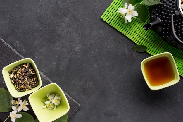Elevated view of dried herb ingredient with teapot on black surface Free Photo