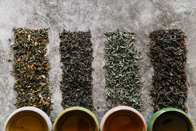 An elevated view of dried herbs with herbal teacups against grey dark backdrop Free Photo