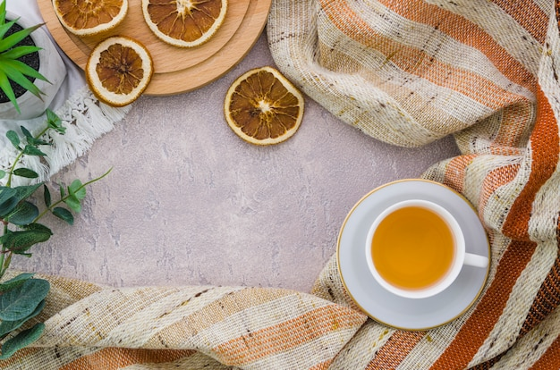 An elevated view of dried lemon slices with stripes textile on concrete backdrop Free Photo