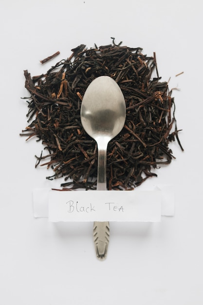 Elevated view of dry black tea leaves with white label on white backdrop Free Photo
