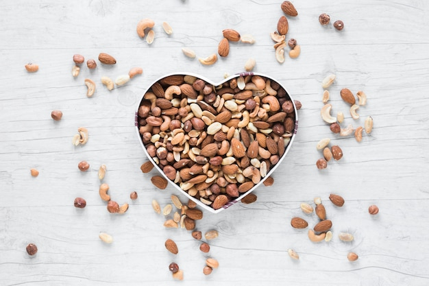 Elevated view of dryfruits in heart shape against wooden desk Free Photo