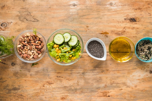 Elevated view of dryfruits; oil; chia seeds and ingredients arranged in a row on wooden table Free Photo