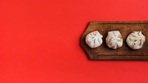 An elevated view of dumplings on wooden tray against red backdrop Free Photo
