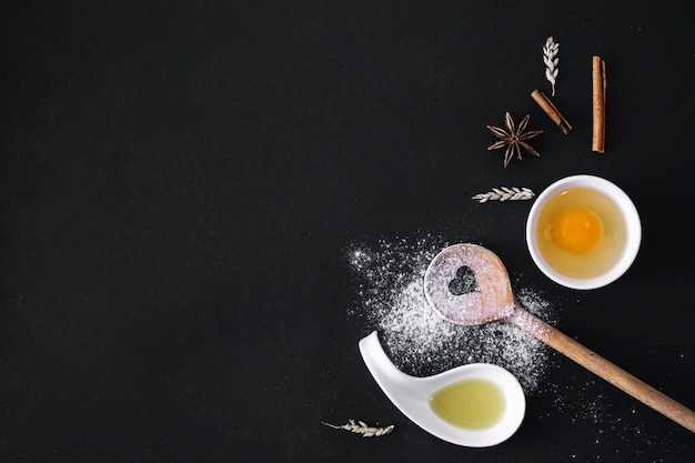 Elevated view of egg; spices; grain; heart shape spoon; flour and oil on black surface Free Photo