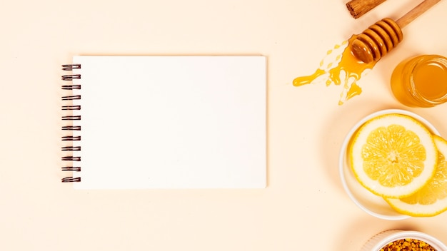 Elevated view of empty notepad with lemon slice and honey Free Photo