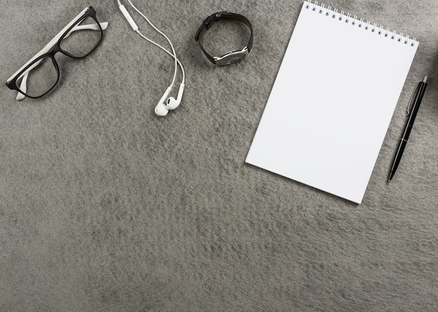 An elevated view of eyeglasses; earphone; wrist watch; spiral notepad and pen on gray desk Free Photo
