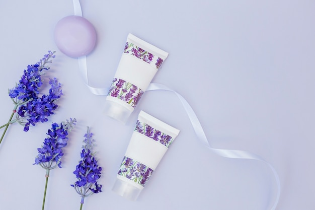 Elevated view of fake lavender flowers; soap; moisturizing cream and ribbon Free Photo
