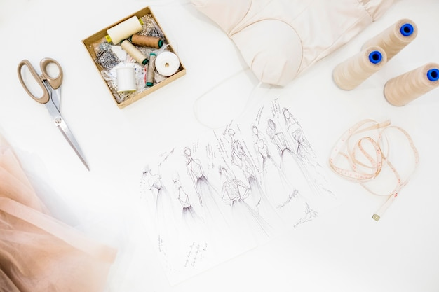 25b1ea3927904 Elevated view of fashion sketch and sewing accessories on white ...