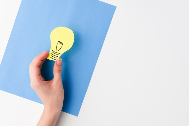 An elevated view of female hand holding light bulb paper cutout over blue card paper Free Photo