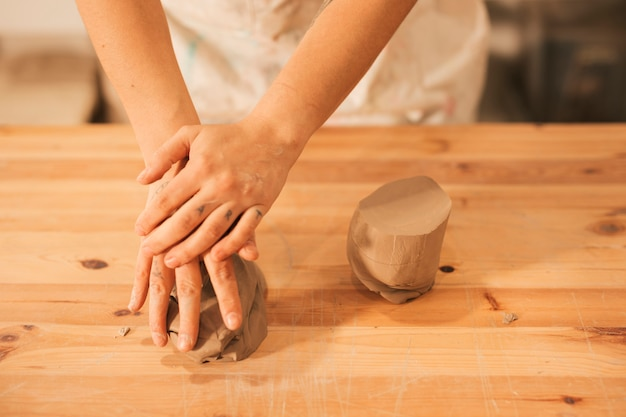 An elevated view of female kneading the clay on wooden table Free Photo