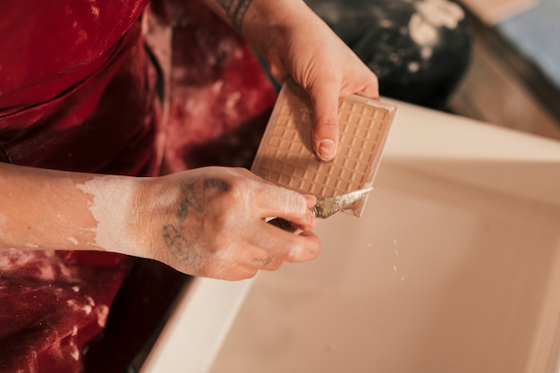 An elevated view of female potter cleaning the paint on tiles with sharp tool Free Photo