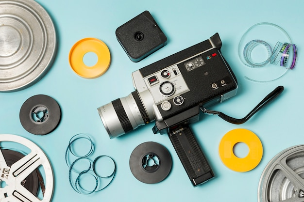 An elevated view of film reel; film strips and camcorder on blue background Free Photo
