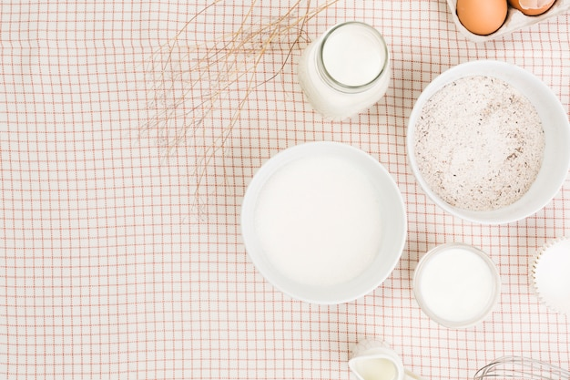 Elevated view of flour; milk; sugar and egg over checkered napkin Free Photo