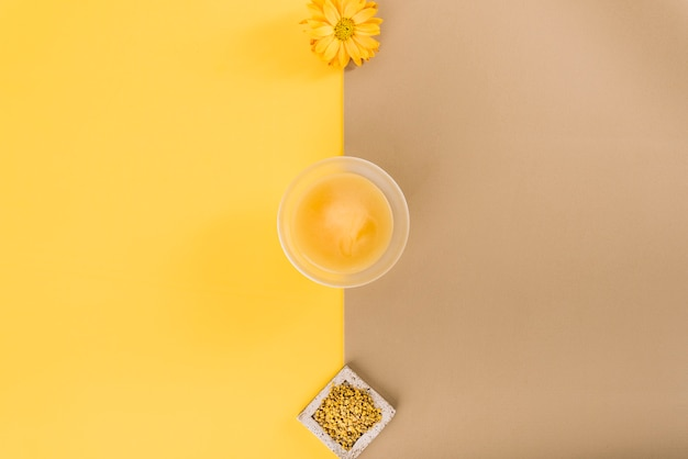 Elevated view of flowers; lemon curd and bee pollen on dual colored background Free Photo