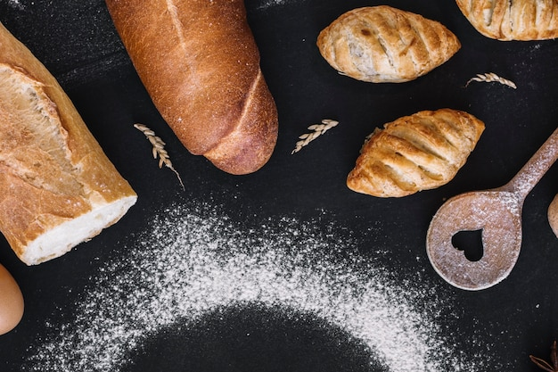 Elevated view of fresh breads; heart shape spoon; grain and flour on black background Free Photo