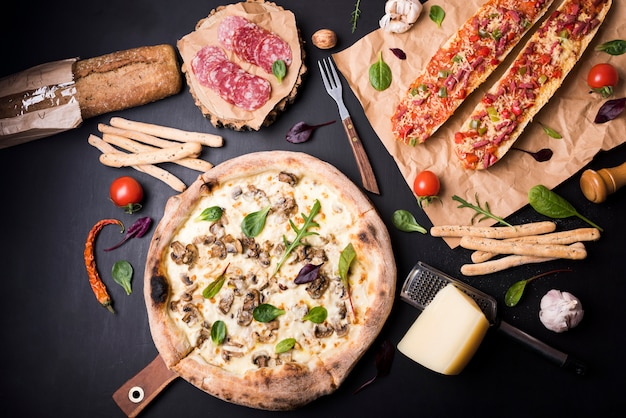 Elevated view of fresh delicious italian food with ingredients on black surface Free Photo