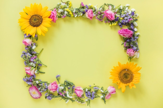 Elevated view of fresh flowers forming frame on yellow surface Free Photo