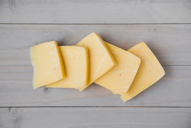 An elevated view of fresh gouda cheese slices on wooden desk Free Photo