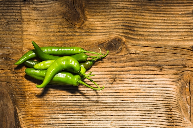 Elevated view of fresh green chili peppers on wooden surface Free Photo
