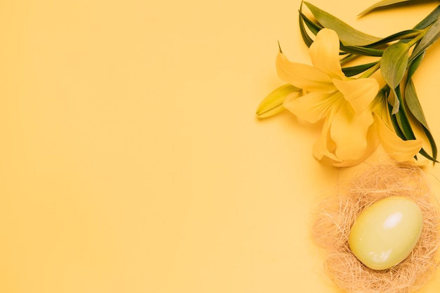 An elevated view of fresh lily flower with easter egg in the nest on yellow backdrop Free Photo