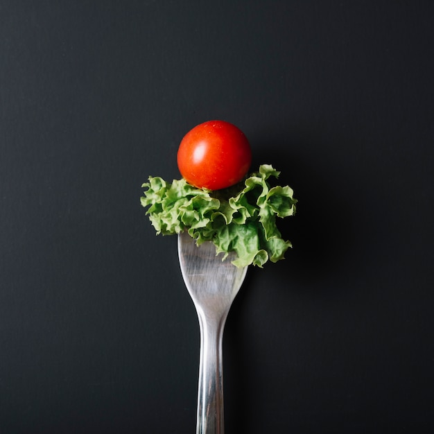 Elevated view of fresh tomato and lettuce with fork on black surface Free Photo