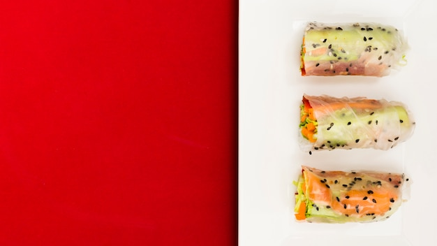 An elevated view of fresh vegetable and salmon fish spring rolls on plate Free Photo