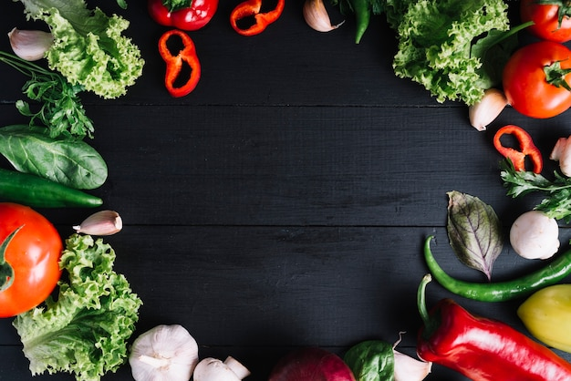 Elevated view of fresh vegetables forming circular frame on black background Free Photo