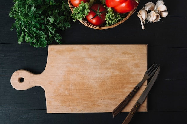 Elevated view of fresh vegetables; garlic cloves; chopping board and eating utensils on black background Free Photo