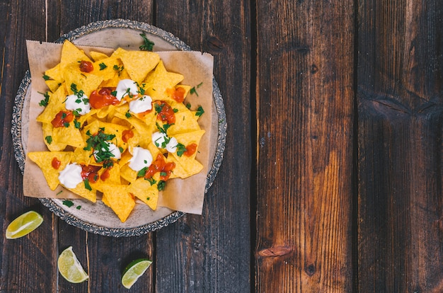 Elevated view of garnished tasty mexican nachos in plate with lemon slices on brown wooden desk Free Photo