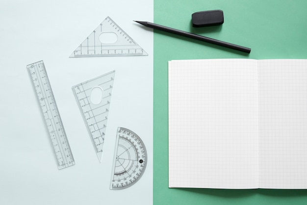 Elevated view of geometric equipment; notebook; pencil and eraser on dual colorful background Free Photo