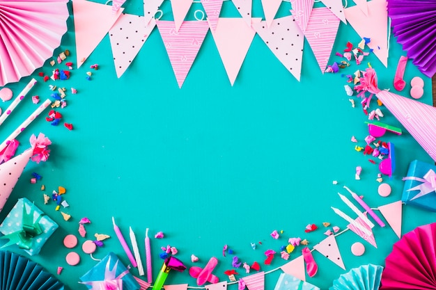 Elevated view of gift boxes and various party accessories on green background Free Photo