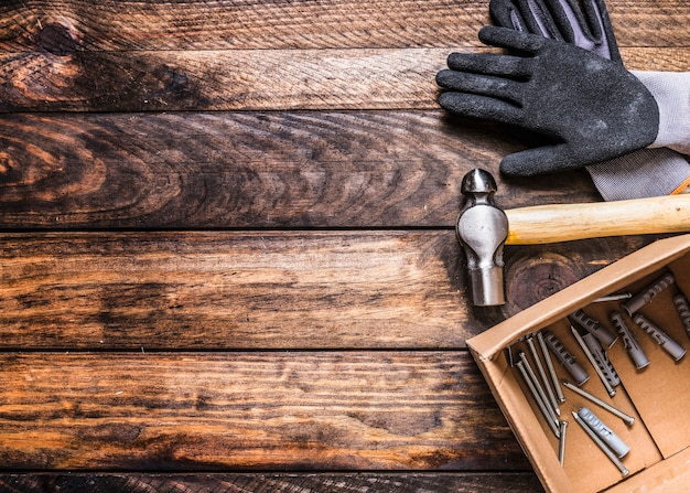 Elevated view of gloves, hammer, nails and wall plugs on wooden background Free Photo