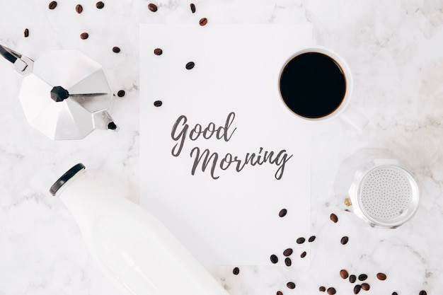 An elevated view of good morning text on paper; cafeteria coffee pot; coffee cup; milk bottle and coffee beans on marble backdrop Free Photo