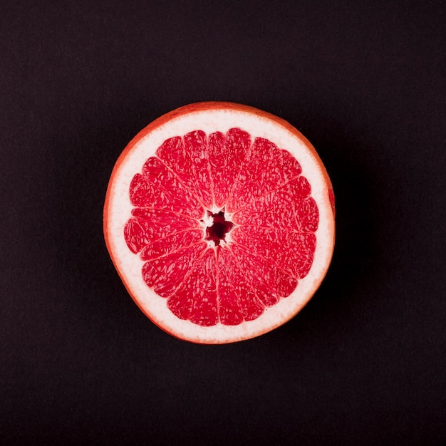 An elevated view of grapefruit cross-section against black background Free Photo