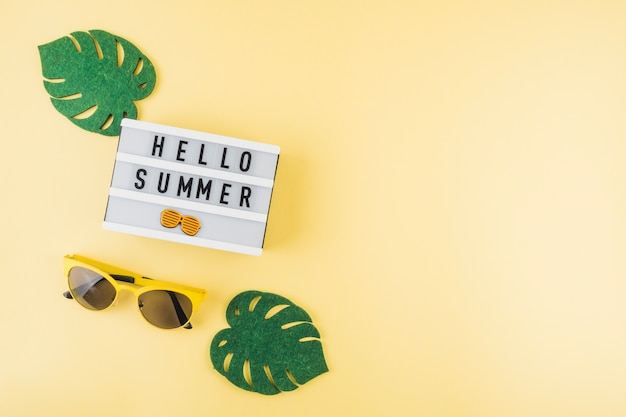 An elevated view of green artificial monstera leaves; sunglasses near the hello summer light box on colored background Free Photo