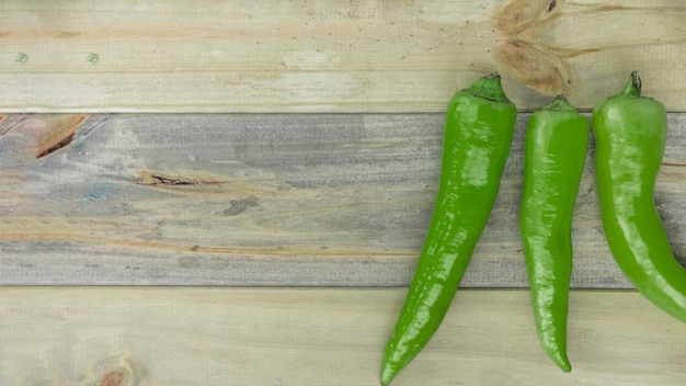 Elevated view of green chili peppers on wooden backdrop Free Photo