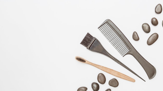 Elevated view of haircomb; pebbles and brush on white backdrop Premium Photo