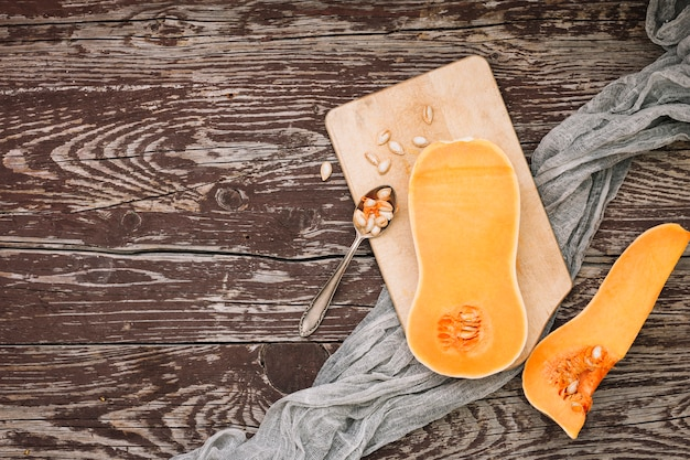 An elevated view of halved butternut squash with seeds on chopping board over the wooden desk Free Photo